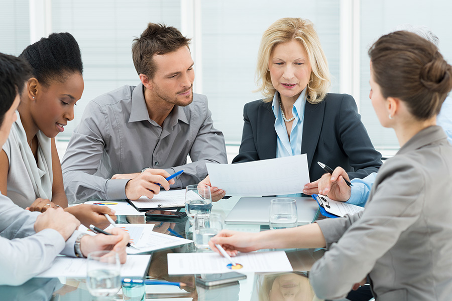 Coworkers discussing documents in a meeting setting